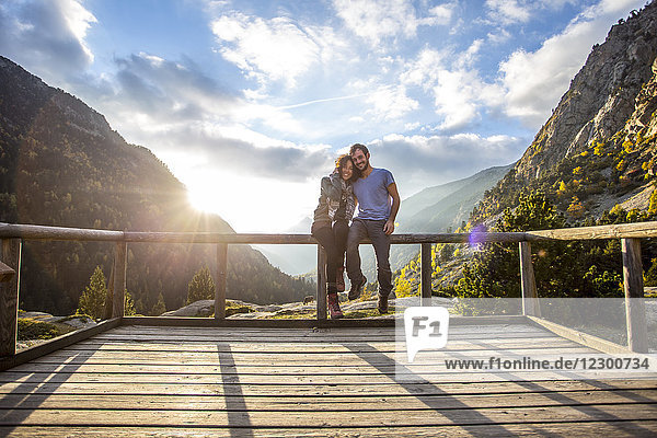 Portrait of young couple embracing on wooden platform in Aiguestortes i Estany de Sant Maurici National Park at sunset,  Aiguestortes,  Lleida,  Spain