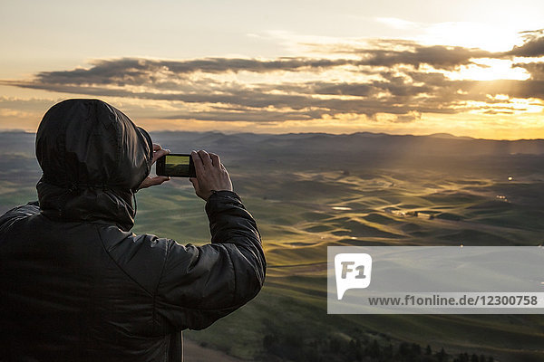 Tourist photographing rolling hills at sunrise  Steptoe Butte State Park  Palouse  Washington State  USA