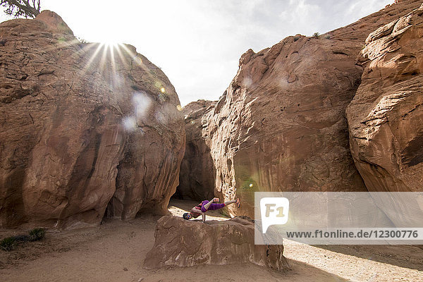 Side view of woman doing yoga in crane pose in front of slot canyon  Grand Staircase-Escalante National Monument  Utah  USA