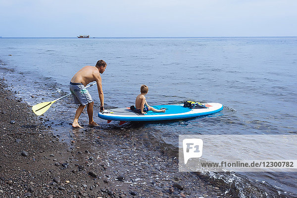 Father and son at sup surfboard Bali Indonesia.