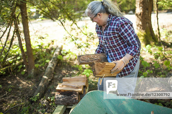 Mature woman with gray hair carrying and stacking firewood