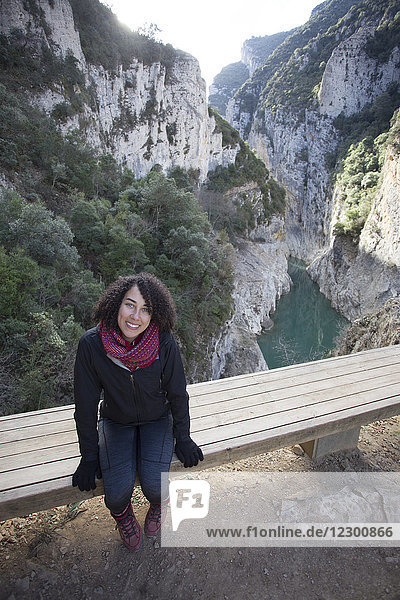 High angle portrait of young woman sitting on bench in Montrebei Gorge and smiling  Montrebei  Lleida  Spain
