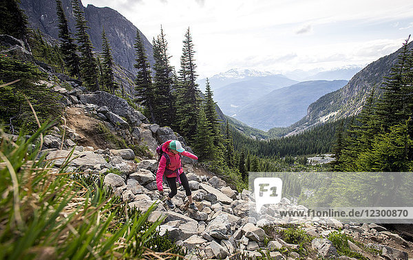 Female hiker descending rocky hill in Garibaldi Provincial Park  British Columbia  Canada