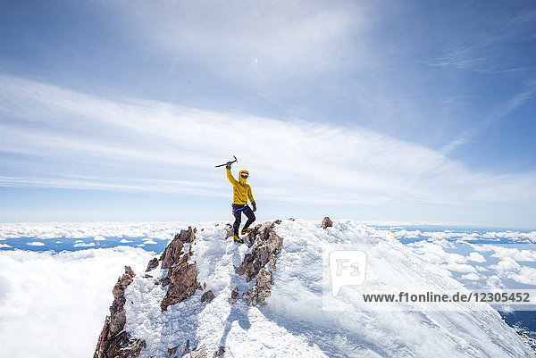 Adventurous mountain climber rising ice pick in victory pose at summit of Mt Shasta  California  USA
