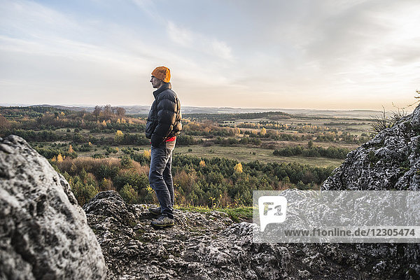 Side view of man standing on rock formation and looking at view,  Polish Jura,  Rzedkowice,  Silesia,  Poland
