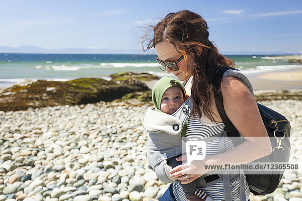 Side view waist up shot of mother with baby son in baby carrier at beach