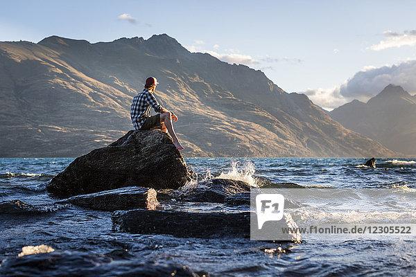 Mountain landscape of man sitting on rock in Lake Wakatipu  Otago  New Zealand
