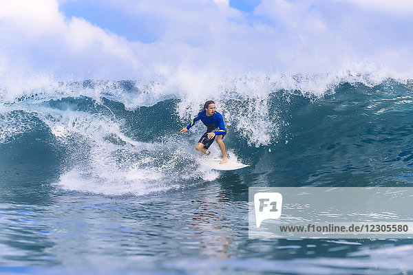 Young man riding wave on surfboard in sea