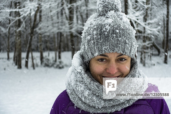Headshot portrait of smiling woman in knit hat and scarf against forest in winter
