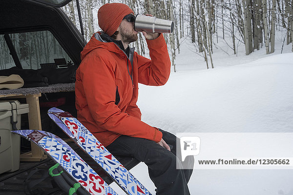 Side view of splitboarder sitting in car trunk and drinking tea from thermos