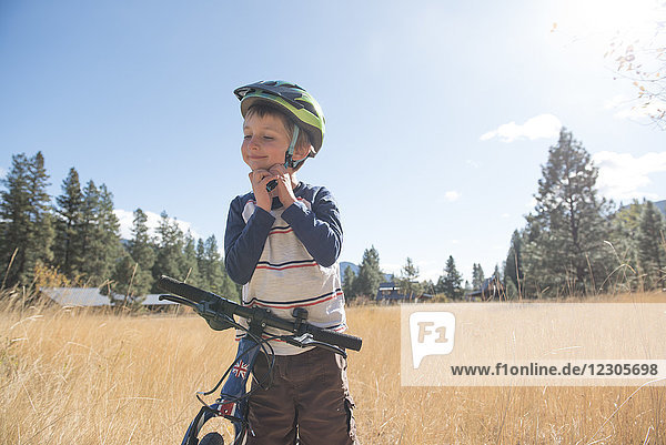 A young boy puts his helmet on for a bike ride in Mazama  Wa.