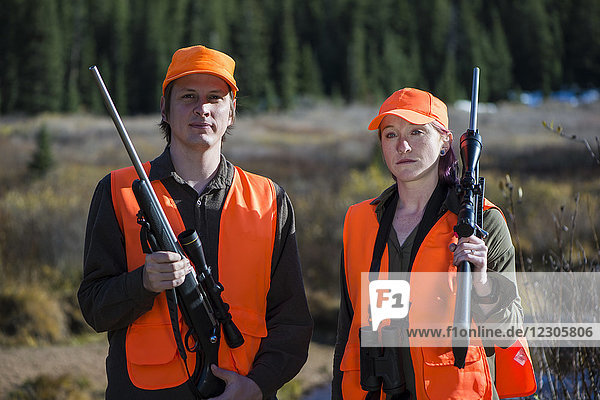 Portrait of male and female hunter posing with hunting rifles  Colorado  USA