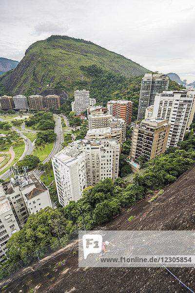 Adventurous man rock climbing Morro do Cantagalo (Cantagalo Mountain) with city in background  Rio de Janeiro  Brazil