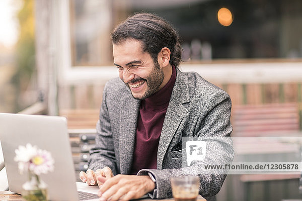 Hispanic male with a beard using a laptop outside at a cafe by the water wearing a blazer and a turtle neck pullover