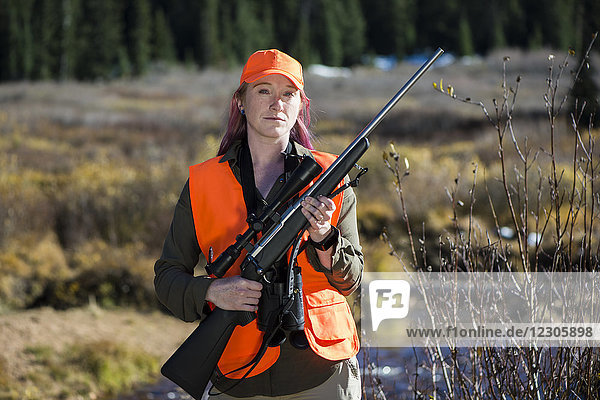 Portrait of female hunter posing with rifle in Guanella Pass  Colorado  USA