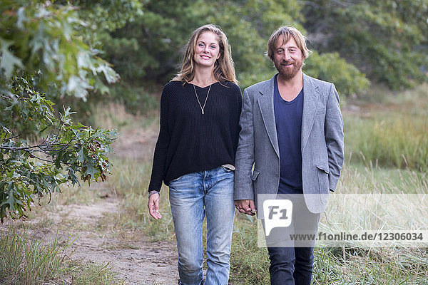 Front view of smiling couple walking in natural setting