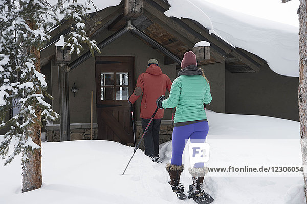 Rear view of couple arriving at mountain cabin on snowshoes  Aspen  Colorado  USA