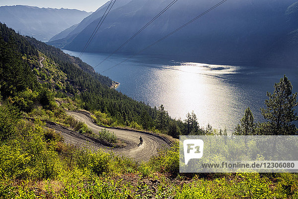 Landscape with motorcyclist going along winding High Line Road  Anderson Lake  D'Arcy  BC  Canada