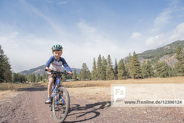 A young boy on a bike on the trails around Mazama  WA