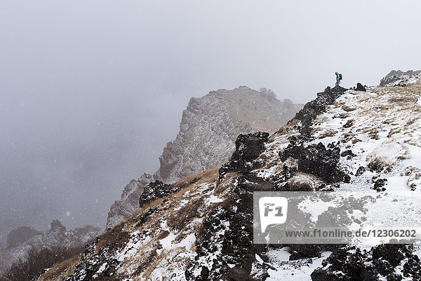 Distant view of female hiker standing at the edge of Valle del Bove  Sicily  Italy