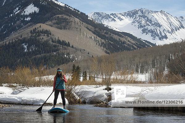 Woman paddleboarding small river in mountains near Aspen  Colorado  USA