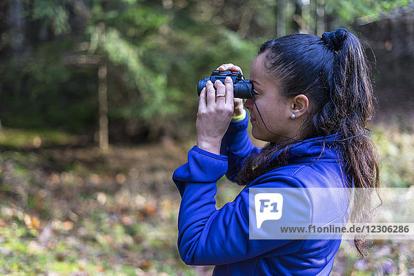 Side view of woman looking through binoculars in forest