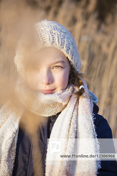Germany  Brandenburg  Lake Straussee  portrait of a girl standing in front of reed