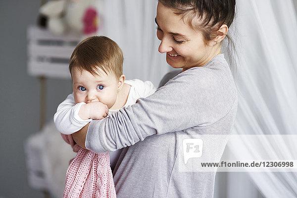 Glückliche Mutter trägt ihr Baby zu Hause.