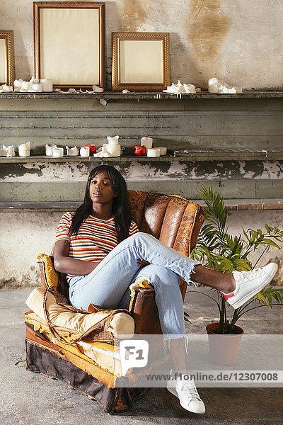 Porträt einer coolen jungen Frau  die auf einem alten Lederstuhl im Loft sitzt.