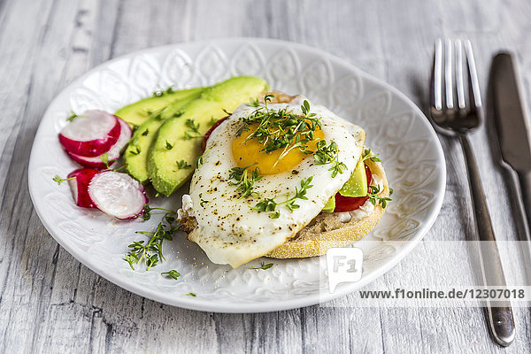 Toast with with fried egg  avocado  red radish  tomato and cress