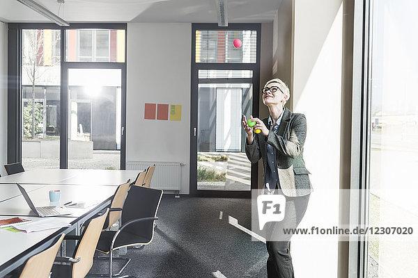 Lächelnde Geschäftsfrau jongliert mit Bällen im Büro