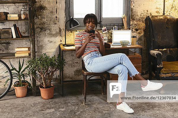 Junge Frau sitzt vor einem Schreibtisch in einem Loft mit Handy