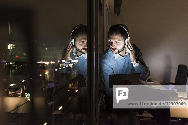 Geschäftsmann sitzt nachts auf der Fensterbank im Büro und hört Musik mit Kopfhörern.