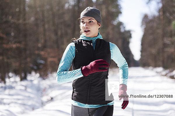 Portrait einer jungen Frau beim Joggen im Winterwald