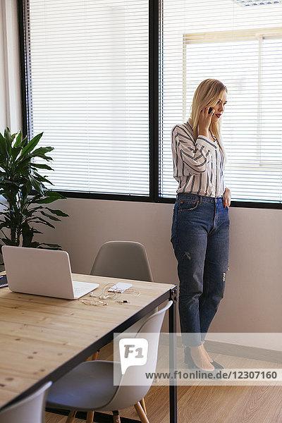 Geschäftsfrau am Fenster stehend  telefonierend