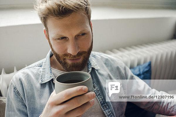 Mann entspannt sich zu Hause  trinkt Kaffee