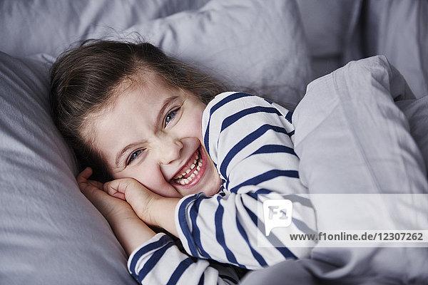 Porträt des lachenden Mädchens im Bett liegend