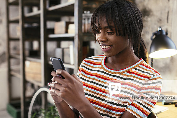 Porträt einer lächelnden jungen Frau in einem Loft mit Handy