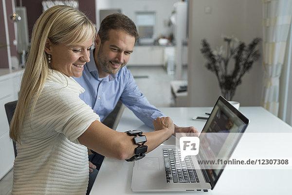 Mann und lächelnde Frau mit tragbarem Arm am Schreibtisch