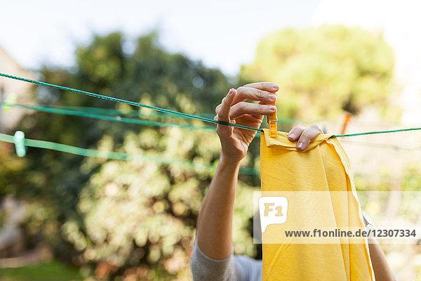 Nahaufnahme einer Frau  die eine gelbe Decke an der Wäscheleine aufhängt.