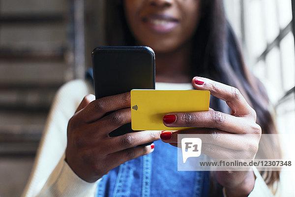 Frauenhände mit Handy und Wifi-Keycard,  Nahaufnahme