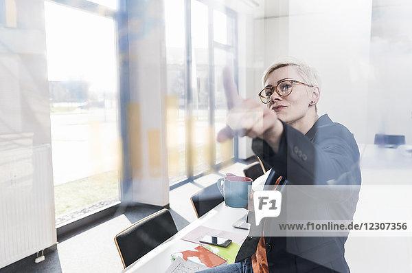 Zuverlässige Geschäftsfrau beim Blick auf die Glasscheibe im Büro