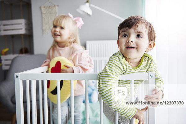 Porträt eines lächelnden Kleinkindes in der Krippe mit seiner Schwester im Hintergrund