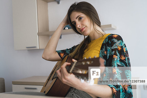 Young woman at home with guitar