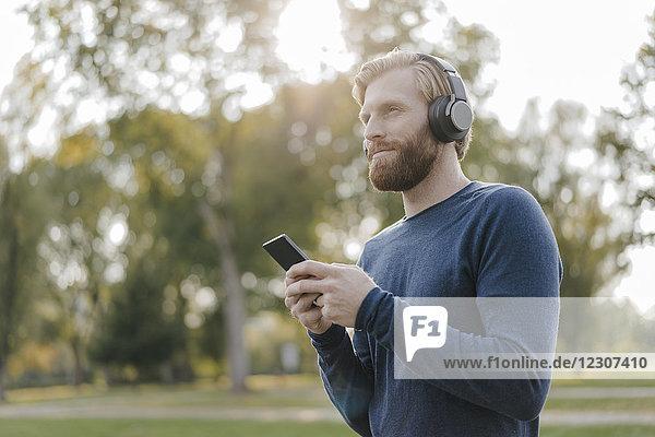 Mann hört Musik mit Kopfhörer und Smartphone im Park