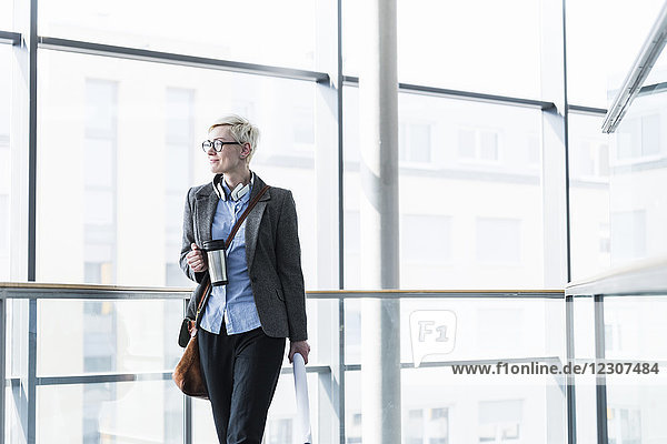 Businesswoman with takeaway cup standing in office building at glass front