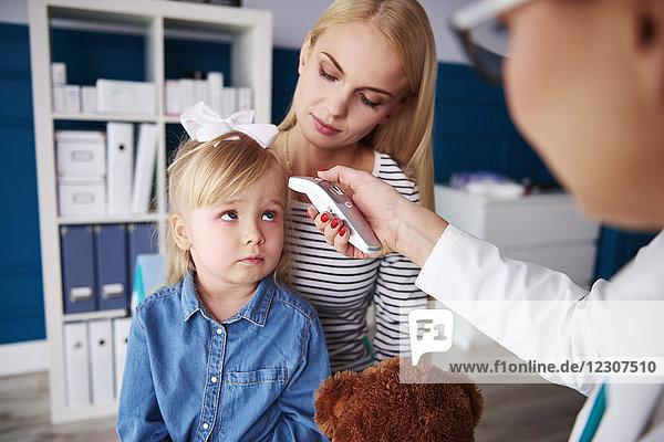 Arzt  der die Temperatur des Mädchens in der Arztpraxis misst.