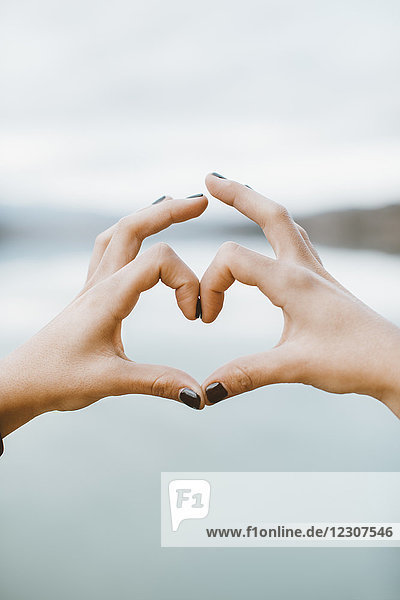 Frauenhände in Herzform vor dem See  Nahaufnahme