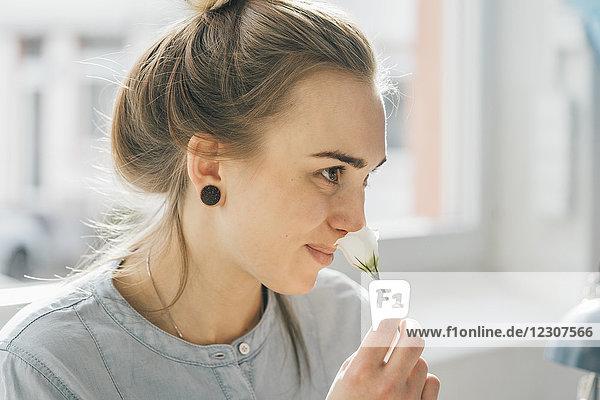 Lächelnde junge Frau riecht Blüte