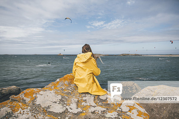 Frankreich  Bretagne  Landeda  Dunes de Sainte-Marguerite  junge Frau auf Felsen an der Küste sitzend